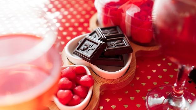 Chocolats et bonbons sur des assiettes en forme de coeur. table de fête pour rendez-vous amoureux. fond rouge