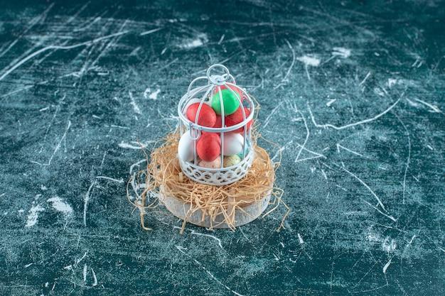 Chocolats colorés dans une cage sur une paille sèche sur le plateau, sur la table bleue.