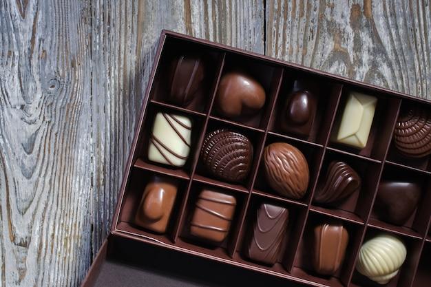 Chocolats de différentes formes et couleurs dans une boîte cadeau sur une table en bois. mise à plat. vue de dessus