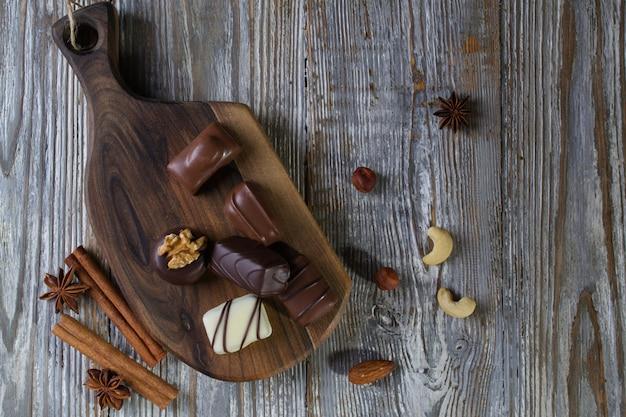 Chocolats de différentes formes et couleurs sur une planche en bois rustique. photo de nourriture atmosphérique