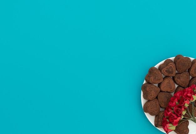 Chocolats en forme de coeur dans un bol blanc sur fond bleu avec des fleurs rouges.