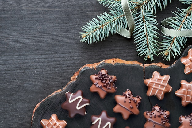 Chocolats en forme d'étoile sur un fond texturé foncé avec des brindilles et des rubans de sapin