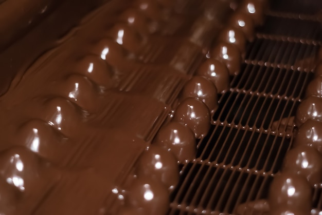 Chocolats juste versés avec du chocolat liquide sur un tapis roulant d'une usine de confiserie close-up