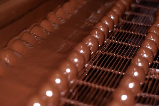 Chocolats juste versés avec du chocolat liquide sur un tapis roulant d'une usine de confiserie