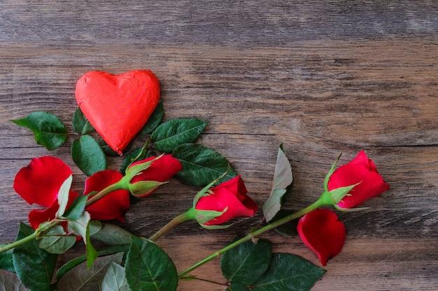 Des chocolats rouges en forme de coeur et des roses placés sur des planchers en bois et laissent la place aux lettres