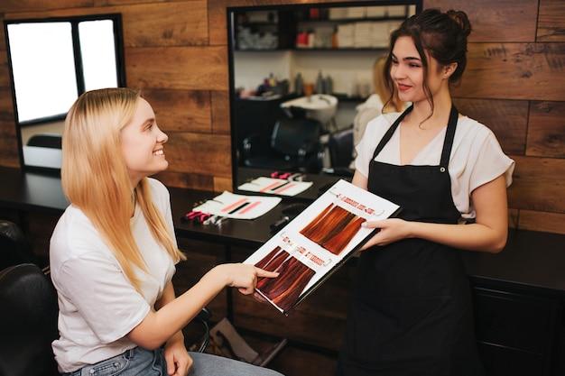 Choise a été faite souriante jeune femme blonde montrant la couleur des cheveux de la palette avant de colorier dans un salon de beauté. beauté, concept de teinture capillaire