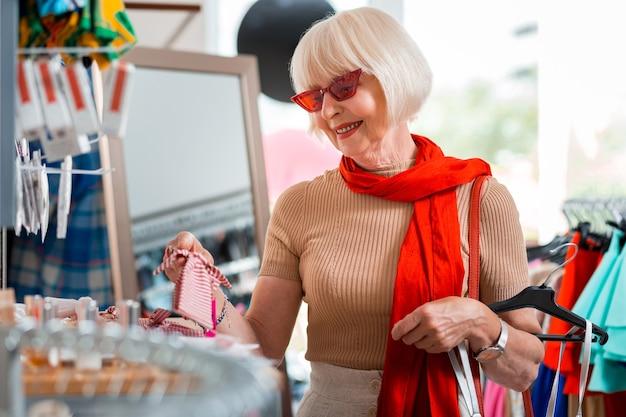 Choisir. attendez l'élégante femme âgée exprimant son intérêt tout en recherchant des vêtements supplémentaires pour sa robe