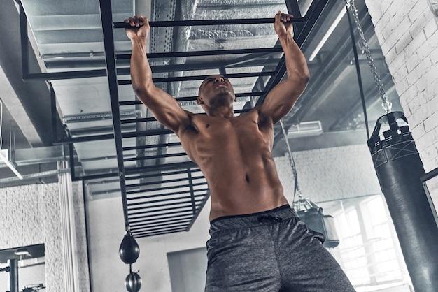 Choisir la bonne direction. beau jeune homme africain faisant des tractions tout en faisant de l'exercice dans la salle de sport