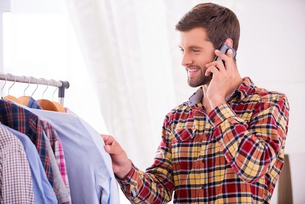 Choisir la chemise à porter. beau jeune homme choisissant une chemise à porter et parlant au téléphone portable