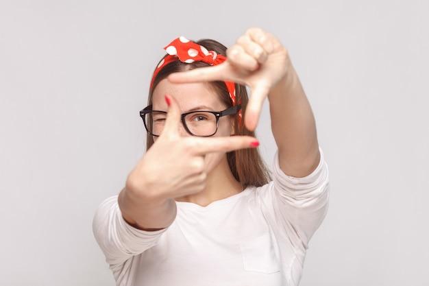 Choisir la composition ou se concentrer sur le portrait d'une belle jeune femme émotive en t-shirt blanc avec des taches de rousseur, des lunettes, des lèvres rouges et un bandeau. tourné en studio intérieur, isolé sur fond gris clair.
