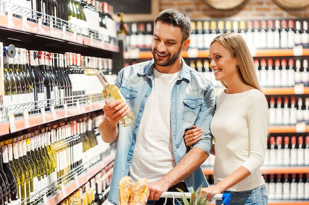 Choisir du vin pour le dîner. heureux jeune couple choisissant du vin ensemble en se tenant debout dans un magasin de vin