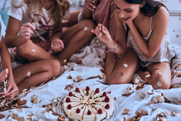 Choisir la meilleure bouchée. quatre jeunes femmes en pyjama se préparent à manger du gâteau tout en organisant une soirée pyjama