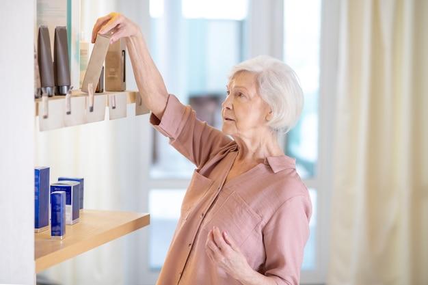 Choisir un parfum. femme mature aux cheveux courts, choisir des parfums dans une boutique