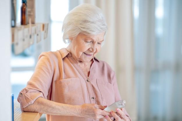 Choisir un parfum. femme mature testant des parfums dans un institut de beauté