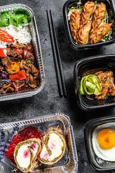 Choisir des plats à emporter. rouleaux de printemps, boulettes, gyoza et nouilles au wok en boîte. emportez et partez avec des aliments biologiques