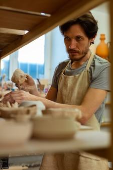 Choisir des pots adaptés. maître professionnel d'argile aux cheveux noirs triant sa collection de pots tout en restant près des étagères
