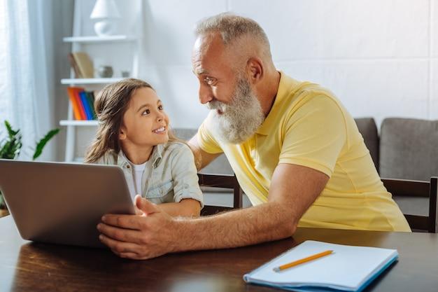 Choisir avec soin. jolie petite fille assise à la table et discutant avec son grand-père souriant de la vidéo à regarder en tenant un écran d'ordinateur portable