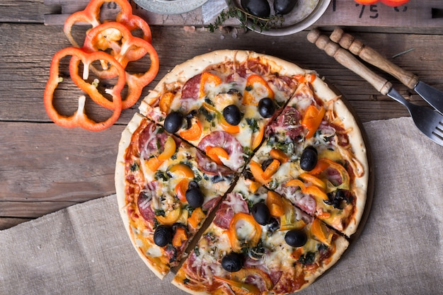 Choisir une tranche de pizza au pepperoni. mains cueillant une tranche de pizza. vue de dessus de la délicieuse pizza au pepperoni chaud sur fond de béton noir