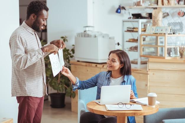 Choisissez-en un. enthousiaste jeune homme tenant deux imprimés avec des concepts de conception de projet à sa collègue et la femme choisissant une meilleure option