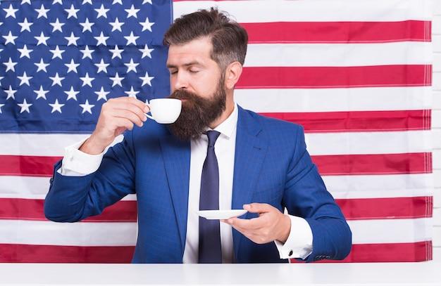 Choisissez la liberté. le politicien boit du café. homme d'affaires barbu patriotique pour les états-unis. bonne fête nationale. les états-unis célèbrent le 4 juillet. apprentissage de la langue anglaise. homme d'affaires avec drapeau américain et café.