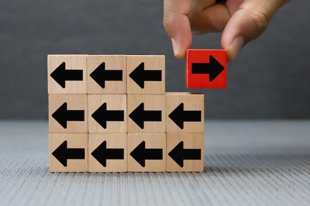 Choisissez à la main des blocs de jouets en bois avec une flèche de couleur noire