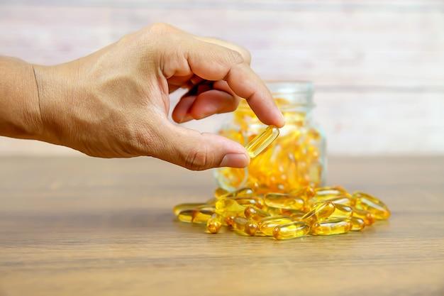 Choisissez à la main une capsule d'huile de foie de morue à partir d'un tas d'huile de foie de morue.