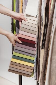 Choisissez à la main les échantillons de tissus d'ameublement colorés dans la boutique
