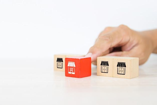 Choisissez à la main une pile de blocs de bois cube avec l'icône de magasin de commerce électronique d'entreprise de franchise.