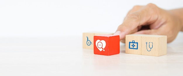 Choisissez la pile de blocs en bois avec une icône saine à la main.