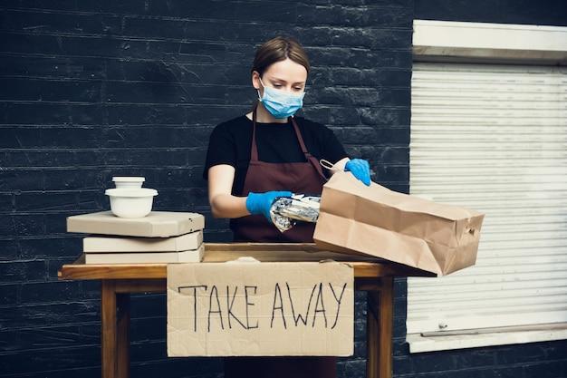 Choisissez la santé. femme préparant des boissons et des repas, portant un masque protecteur, des gants. service de livraison sans contact pendant la pandémie de coronavirus de quarantaine. concept à emporter. tasses, emballages recyclables.