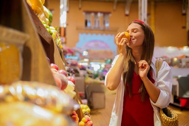 Choix agréable. une femme sentant des fruits dans un magasin et ayant l'air impliquée