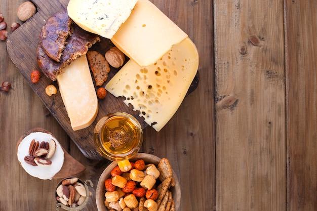 Choix classique de fromages différents, sur une vieille planche de bois et des noix. fromage différent sur une vieille planche de bois. fromage et bière néerlandais