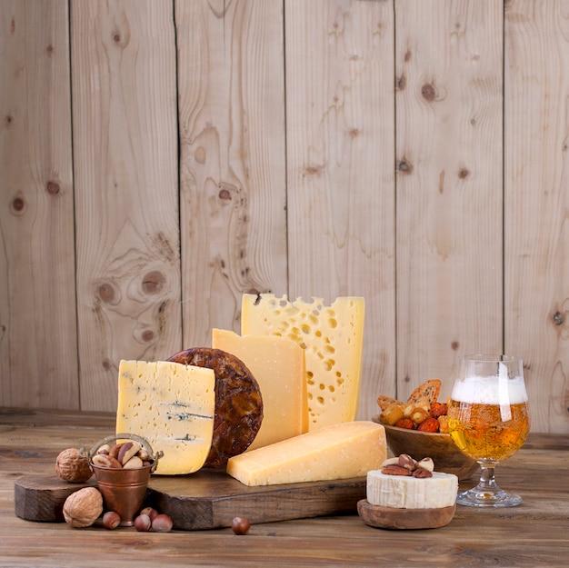 Choix de fromages classiques différents, sur une vieille planche de bois, des noix, des collations et un verre de bière