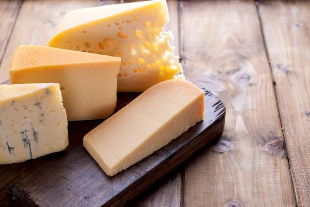 Choix de fromages classiques différents, sur une vieille planche de bois