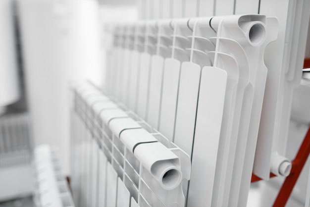 Choix de radiateurs de chauffage à eau sur vitrine en magasin de plombier.