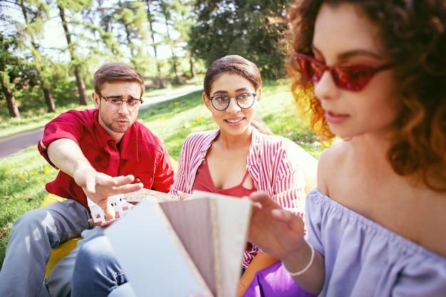 Choix sérieux. joyeuse femme brune assise en plein air avec ses collègues et discutant de leur démarrage