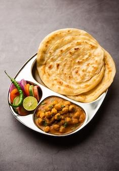 Chole ou chana masala avec paratha, cari épicé aux pois chiches servi avec laccha parantha. plat populaire de l'inde du nord