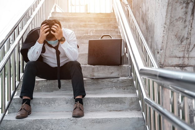 Les chômeurs ont souligné le jeune homme d'affaires asiatique en costume couvrant le visage avec les mains. concept d'échec et de licenciement à la maladie covid-19, travail et stress. les gens d'affaires désespèrent faible crise économique