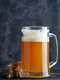 Chope de bière de blé non filtrée sur un fond de béton foncé et des épis de blé