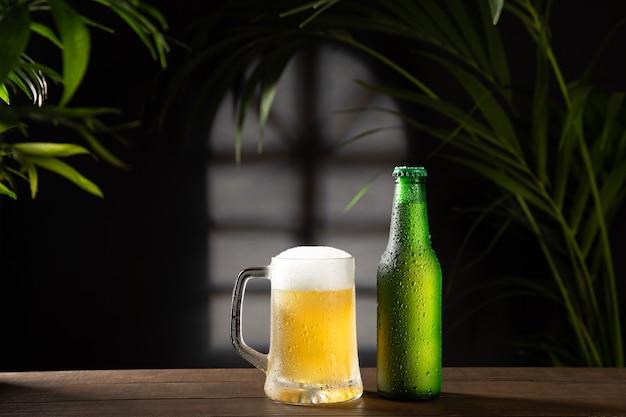 Chope de bière et bouteille sur fond sombre sur socle en bois.