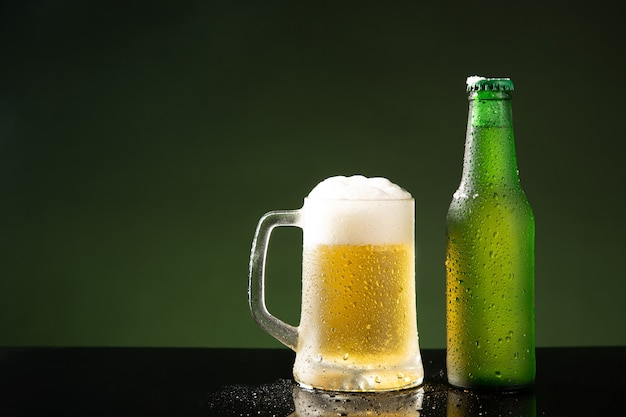 Chope de bière et bouteille sur fond vert avec fond.