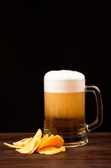 Chope de bière avec des frites sur une planche de bois
