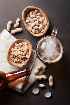 Chope à bière lager, bouteille et collations sur une table en pierre
