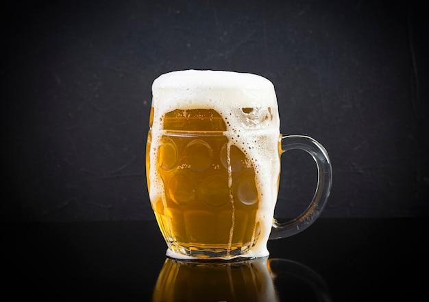 Chope de bière légère sur fond sombre. bière artisanale non filtrée