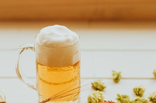 Chope de bière avec de la mousse sur une table blanche