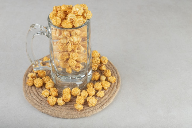 Chope de bière posée sur un dessous de plat, rempli de pop-corn aromatisé au caramel, sur marbre.