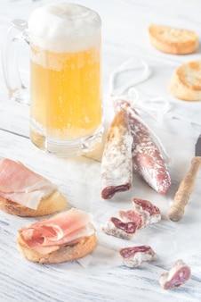 Chope de bière avec sandwichs et saucisse fumée