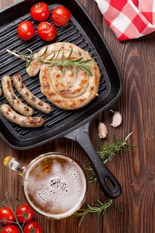 Chope de bière et saucisses grillées sur table en bois. vue de dessus