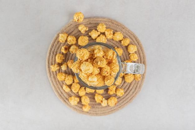 Chope de bière trop remplie sur un dessous de plat avec des morceaux de maïs soufflé à saveur de caramel éparpillés, sur une table en marbre.