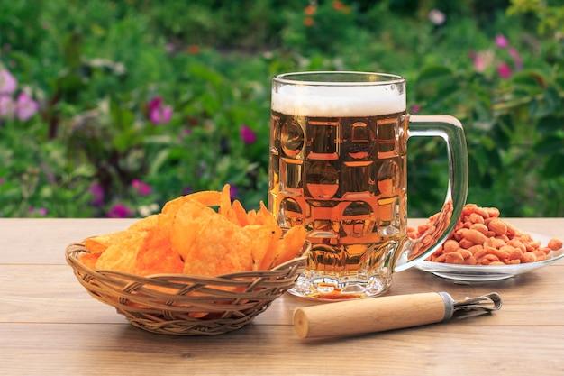 Chope de bière en verre sur table en bois avec croustilles dans un panier en osier, arachides en assiette, ouvreur